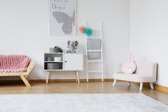 Pink rabbit cushion. Decorative pink rabbit cushion lying on bright small sofa in baby room royalty free stock photo