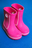 Pink rain boots. Wet pink rain boots on blue background Stock Photos