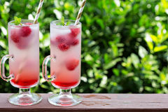 Pink raspberry lemonade in tall glasses. Pink refreshing cold raspberry lemonade in tall glasses outside on the porch Royalty Free Stock Images