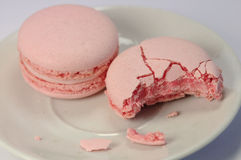 Pink raspberry macarons, half eaten Stock Photography