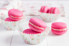 Pink raspberry macaroons on white wooden background Royalty Free Stock Photo