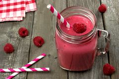 Pink raspberry smoothie against rustic wood. Pink raspberry smoothie in a mason jar with straws on a rustic wood background Royalty Free Stock Image