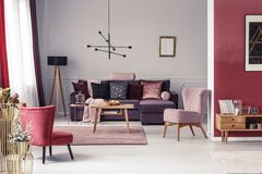 Warm red living room. Pink and red armchair in warm living room interior with pillows on settee against the wall with poster Stock Image