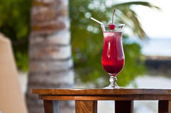 Pink - red drink by turquoise sea. Glass with a cold drink at a beach Stock Images
