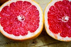 Red grapefruit. Pink Red grapefruit cut on black slate background stock photography