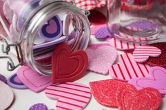Pink and red hearts falling from glass container on white background - valentine`s day concept. Closeup of pink and red hearts falling from glass container on stock photos