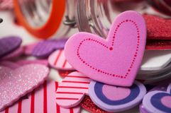 Pink and red hearts falling from glass container on white background - valentine`s day concept. Closeup of pink and red hearts falling from glass container on stock images