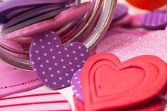 Pink and red hearts falling from glass container on white background - valentine`s day concept. Closeup of pink and red hearts falling from glass container on royalty free stock images