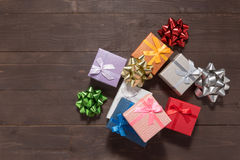 Pink, red, orange, purple, grey, blue and white gift boxes are o. N the wooden background with empty space Stock Photo