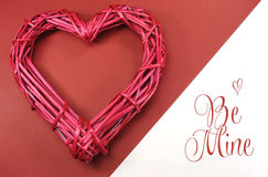 Pink red rattan cane love heart on red and white background with Be Mine message royalty free stock image