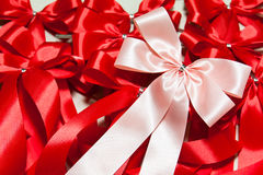 Pink and red ribbons. Pink ribbon bow on red ribbons background Stock Photos