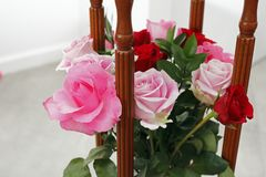 Pink and Red Roses Arrangement with Wood. Beautiful pink and red roses flowers bouquet in between four wooden columns of a side table. Pink and red roses flowers stock photo