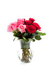 Pink and red roses in a clear vase on white Royalty Free Stock Photography