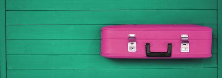 Pink retro suitcases on the wooden green background. Pink retro suitcases on the wooden grey background. Vintage travel luggage. Space for text. Flat lay Stock Image