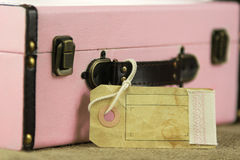 Pink retro vintage suitcase with blank paper tag Royalty Free Stock Photography