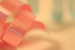 Pink Ribbon. A close up curl of pink ribbon on a soft background Stock Image
