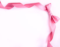 Pink ribbon with bow on the white background Royalty Free Stock Photo