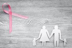 Pink ribbon for breast cancer awareness near paper silhouette of family on grey wooden background top view copyspace Stock Photo