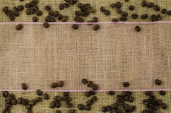 Pink ribbon with coffee beans on linen background. Beautiful pink ribbon with coffee beans on linen background Royalty Free Stock Photography