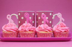 Pink ribbon cupcakes with polka dot coffee mugs Royalty Free Stock Photography