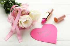 Pink ribbon with flowers, pomade. And inscription Breast Cancer on wooden table Stock Image