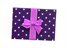 Pink ribbon gift bow on purple gift box. Fancy pink ribbon gift bow with white stitching on purple gift box with polka dots isolated on white background Royalty Free Stock Photography