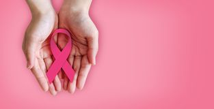 Pink ribbon on hands for breast cancer awareness. With copy space