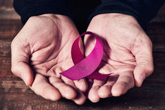 A pink ribbon in the hands of a man Stock Images