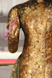 A pink ribbon is hooked to the hand of a statue of Buddha (Thailand) Stock Photo