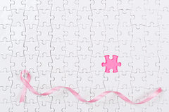 Pink ribbon and puzzle pieces breast cancer. Stock Image
