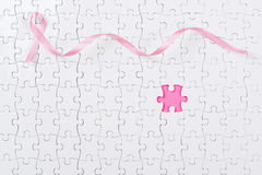 Pink ribbon and puzzle pieces breast cancer. Stock Photo