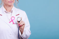 Pink ribbon with stethoscope on medical uniform. Stock Photo