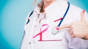 Pink ribbon with stethoscope on medical uniform. Stock Photo