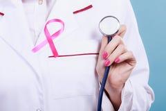 Pink ribbon with stethoscope on medical uniform. Royalty Free Stock Image