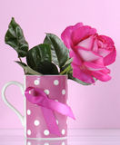 Pink Ribbon symbol on coffee mug with rose - vertical Royalty Free Stock Photography