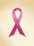 Pink ribbon symbol of the fight against cancer. On pastel colored textured background Royalty Free Stock Photography