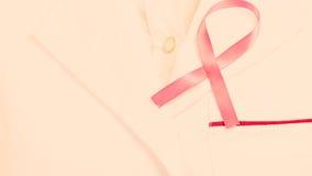 Pink ribbon on white medical apron. Royalty Free Stock Photos