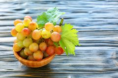 Pink ripe grapes in a wooden bowl. Royalty Free Stock Photos