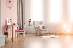 Pink room with dressing table. And white armchair stock photos