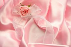 Pink Rose. A pink rose with a glittering white ribbon lying on pink satin fabric - can be used for wedding or the birth of a girl Stock Photo