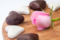 Pink rose with black and white heart cookies on the wooden board Royalty Free Stock Photos
