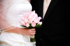 Pink rose brides bouquet. Bride holding a bouquet of pink roses with bride & groom in background Royalty Free Stock Images