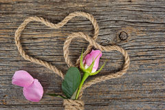 Pink rose bud with rope hearts Stock Photography