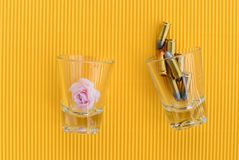 Pink rose and bullets in glass on yellow background Stock Photo