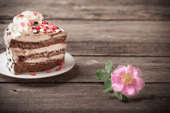 Pink rose and cake on wooden background Stock Photo