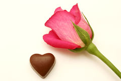 Pink rose and chocolate heart. On a white background Royalty Free Stock Photo