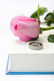 Pink rose and engagement ring on the opened book paper Royalty Free Stock Photography