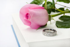 Pink rose and engagement ring on the opened book paper Royalty Free Stock Photos