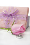 Pink rose and engagement ring beside pink gift box with bow Royalty Free Stock Photos