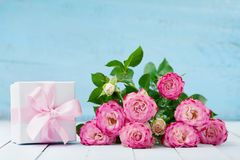 Pink rose flower bouquet and gift box with ribbon on blue table. Greeting card for Birthday, Woman or Mothers Day. Pastel color. Pink rose flower bouquet and Royalty Free Stock Image